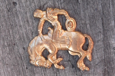 Brass Stamping of a Cowboy Riding a Bronco